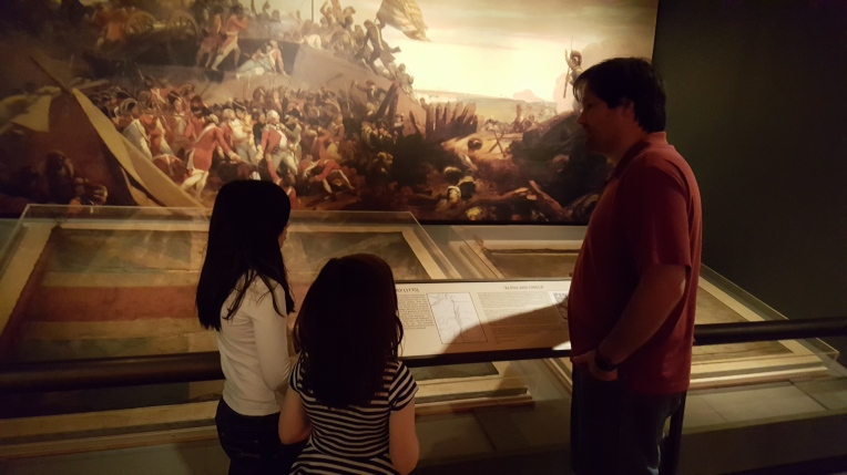 Alpha and Omega Exhibit, Adam explains the historical significance to the girls.